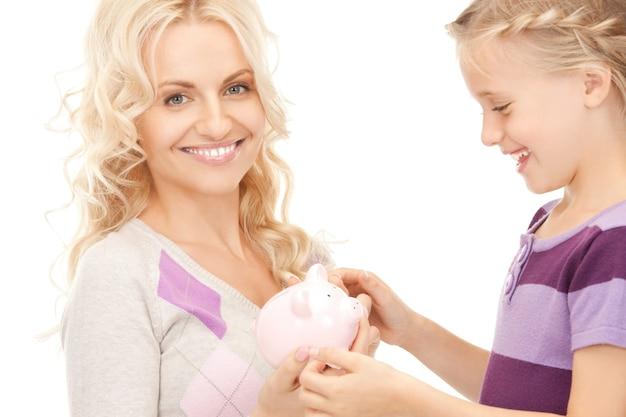 貯金箱を持つ母と少女の写真(女性に焦点を当てる)
