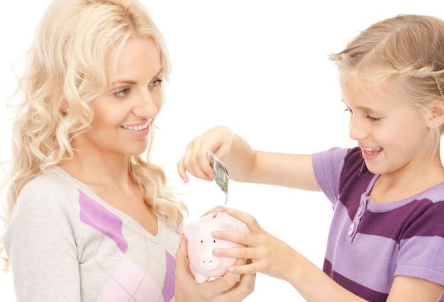 貯金箱を持つ母と少女の写真