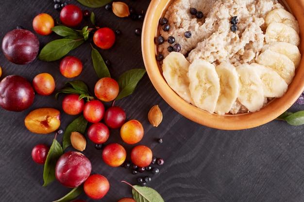 暗い木製の表面、家族、健康的な食事のためのおいしい、健康的な朝食で分離された白いプレートにバナナとブルーベリーのオートミールの写真。黒いテーブルの上の果物の正面図。