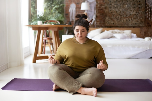 Картина мирной, спокойной молодой пухлой женщины, сидящей босиком на коврике для йоги дома, делая жест мудры и медитируя с закрытыми глазами. баланс, медитация, гармония, дзен и концепция благополучия