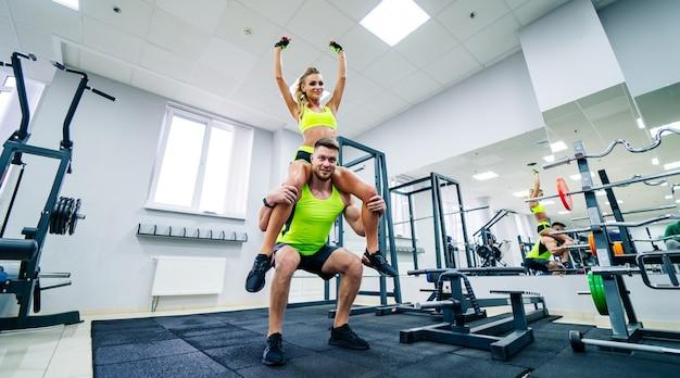 Изображение личного фитнес-тренера и клиентки в тренажерном зале, позирующем перед камерой. концепция здорового образа жизни и фитнеса. девушка сидит на плече мужчины в позе победителя.