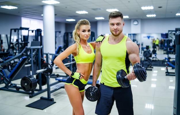 カメラの前でポーズをとっているジムのパーソナルフィットネストレーナーと女性クライアントの写真。健康的な生活とフィットネスの概念。