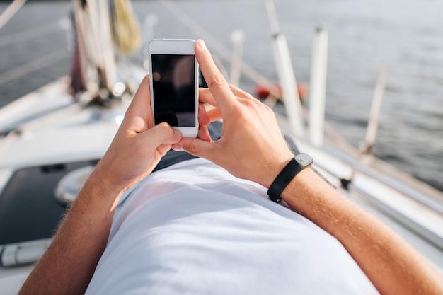 남자의 손에 있는 전화의 그림입니다. 그는 확신을 가지고 있습니다. 화면이 어둡습니다. 전화는 흰색입니다. 젊은 남자는 요트 보드에 누워