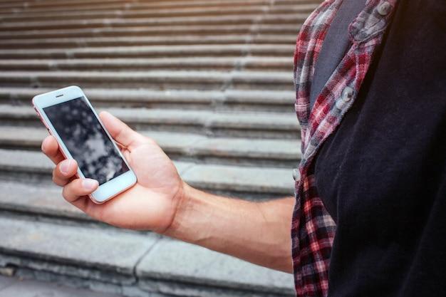 右の男の手の電話の写真。彼は階段のそばに立っています。男はシャツを着ています。