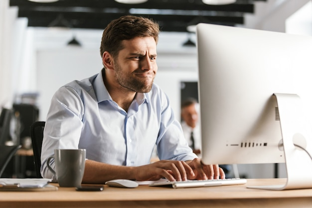 オフィスのテーブルのそばに座ってコンピューターを使用して遊び心のあるビジネスマンの写真