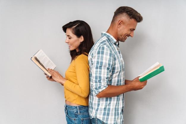 Изображение довольных оптимистичных счастливых улыбающихся взрослых влюбленных, изолированных на серых стенах, читая книги.