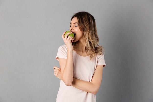 グレーの上に目を閉じて新鮮なリンゴを食べるtシャツの喜んでいる女性の写真