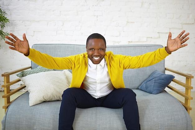 広い笑顔で、あなたを抱きしめるように手を上げ、友好的な興奮した表情を持ち、良いニュースを喜んでいる、ポジティブで感情的な若いアフリカ系アメリカ人男性の写真。人間の感情と感情