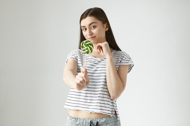 スパイラルカラフルな甘いハードキャンディーで手を差し伸べる光沢のある黒髪のポジティブな幸せな20歳の女性の写真。人、食べ物、栄養、ダイエット、お菓子のコンセプト