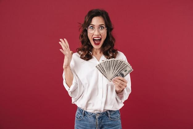 Картина положительного крика удивила молодая женщина, изолированная на красной стене, держащей деньги.