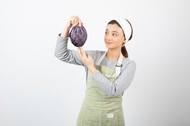흰색에 보라색 양배추를 보고 긍정적인 여자의 그림