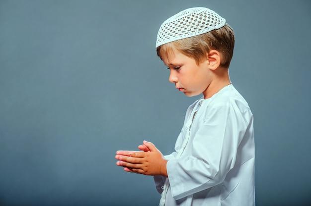 Изображение молящегося ближневосточного мальчика.