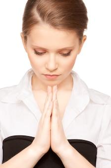 白の上に祈る10代の少女の写真