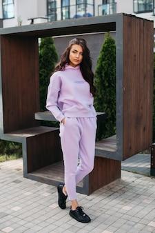 Фотография красивой кавказской девушки в фиолетовом спортивном костюме и черных кроссовках держит руки в карманах