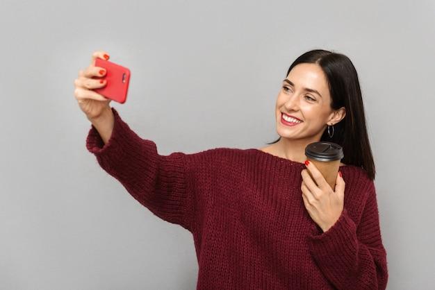 Картина довольно молодой женщины, одетой в бордовый свитер, делает селфи по мобильному телефону изолированного питьевого кофе.