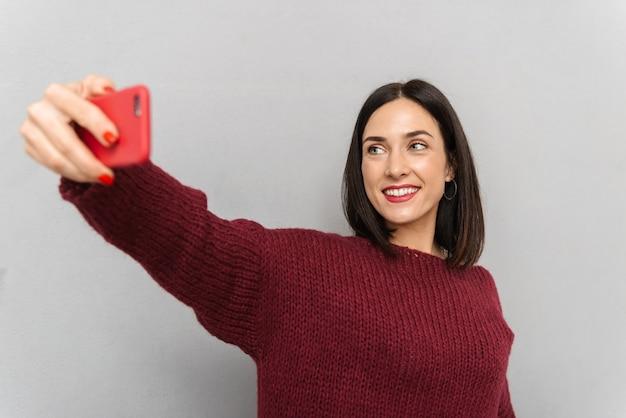 Изображение довольно молодой женщины, одетой в бордовый свитер, делает селфи по мобильному телефону изолированы.