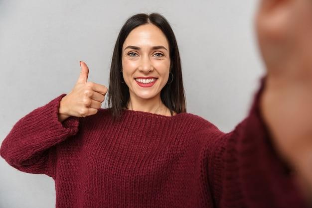 Фотография симпатичной молодой женщины в бордовом свитере, делающей селфи