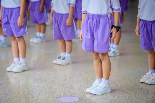 幼稚園で並んで立って病気を防ぐために間隔を空けて立っている小学生の写真covid-19ウイルススタンドと社会的距離