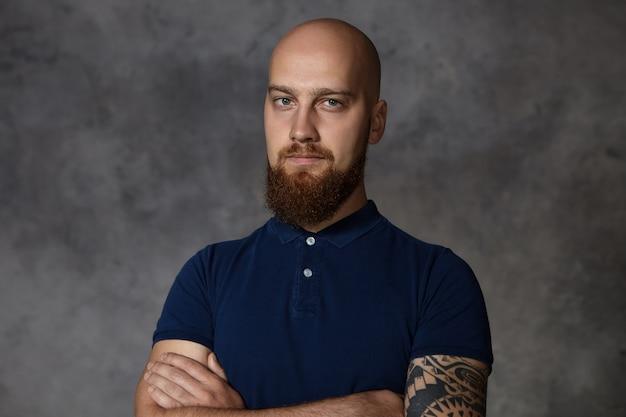 Фотография уверенного в себе молодого бородатого парня с татуировкой, позирующего в закрытой позе в закрытом помещении, скрестив руки на груди, не верит вам, чувствуя уверенность во время спора. язык тела