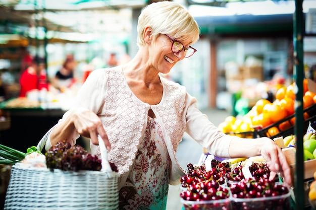 Изображение старшей счастливой женщины на рынке, покупающей овощи и фрукты