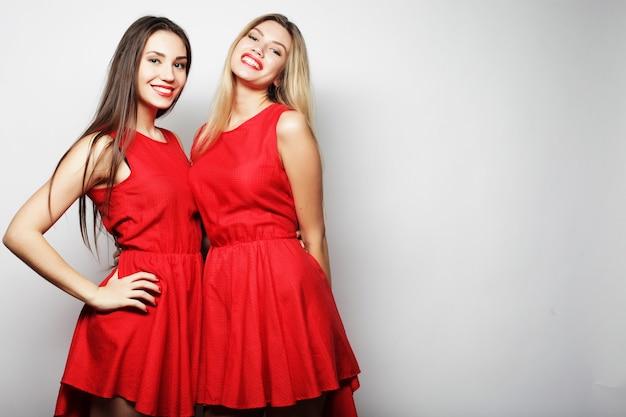 白い背景の上の赤いドレスで官能的な若い女の子の画像