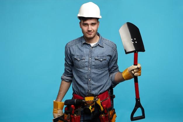 黄色の手袋を着用している深刻なまたは疲れた若い男性の掘削機の写真