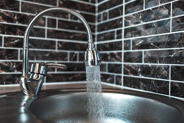 キッチンエリアの流しに水を注いでいる銀色の開いた蛇口の写真。暗いレンガの壁の背景に。