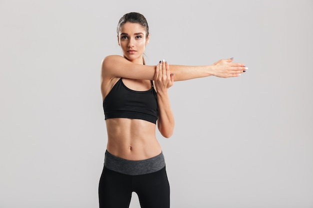 Изображение стройной красивой женщины, делающей занятие аэробикой и растягивающей ее тело, изолированное по серой стене
