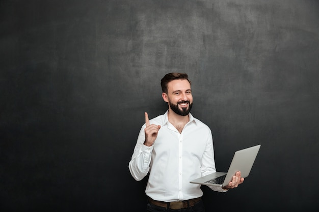 손가락으로 몸짓 실버 노트북을 사용하여 사무실에서 일하는 스마트 갈색 머리 남자의 그림은 어두운 회색 벽 위에 절연