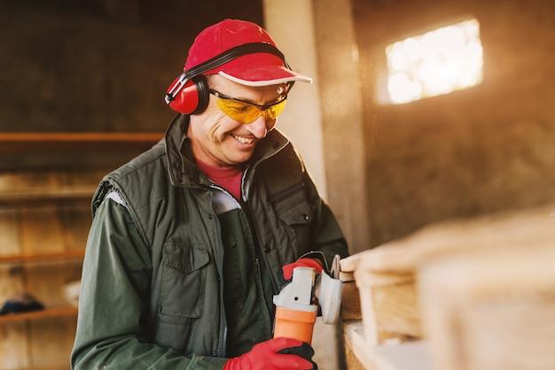 電動グラインダーを使用して木材を形作る保護ユニフォームで成熟した大工の男を笑顔の写真。晴れた日に彼の作業ガレージで彼の仕事を楽しんでいます。