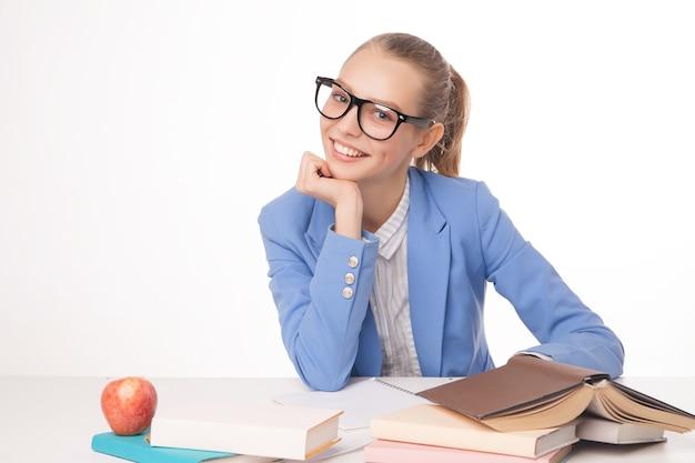 本のスタックで笑顔の学生の写真。孤立。