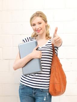 親指を立ててラップトップで笑顔の10代の少女の写真