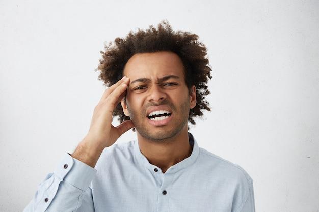 頭痛のある正式なシャツを着たストレスのたまった若い従業員の写真