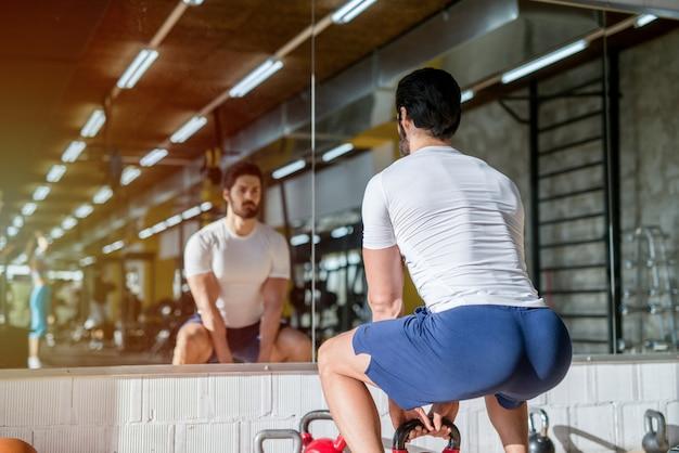 Фотография сильного сосредоточенного молодого человека, делающего приседания с весом в тренажерном зале. стоя перед зеркалом.