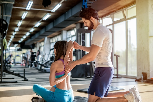 トレーニング後に女性のクライアントが筋肉を伸ばすのに役立つ強力なハンサムなパーソナルフィットネストレーナーの写真。