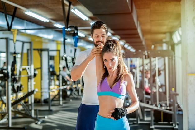 女性のクライアントが腕を伸ばすのを助ける強力なスポーティなパーソナルトレーナーの写真。ジムでのトレーニング。