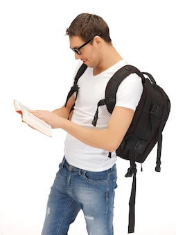 バックパックとスペックの本を持つ学生の写真