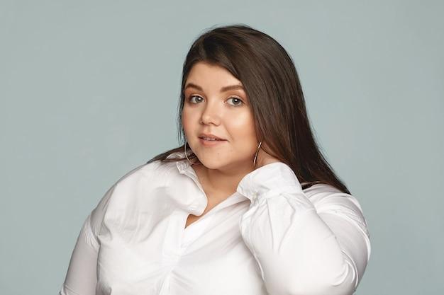 白いシャツと大きな丸いイヤリングを首に触れているスタイリッシュな若い太りすぎの女性従業員の写真。きちんとした美しいぽっちゃり女性ポーズ