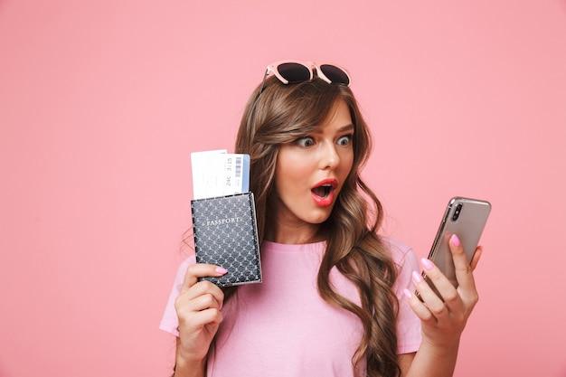 Изображение удивленной девушки-путешественницы 20-х, потрясенно смотрящей на мобильный телефон, держа в руках паспорт и авиабилеты, изолированные на розовом фоне