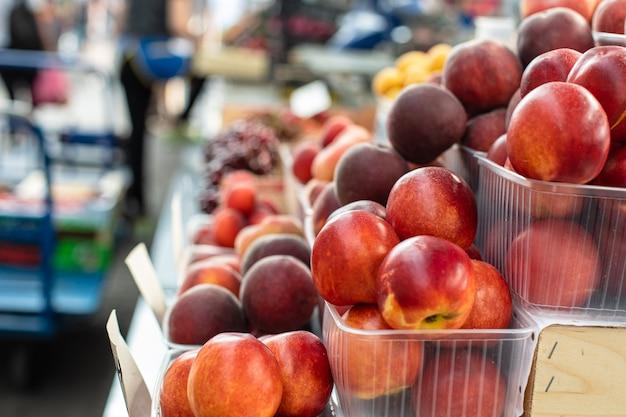 Картина сладких, вкусных и свежих персиков, лежащих в маленьких пластиковых коробках в магазине.