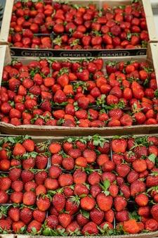 Картина сладкой, вкусной, красной и свежей клубники, лежащей в деревянных ящиках в магазине