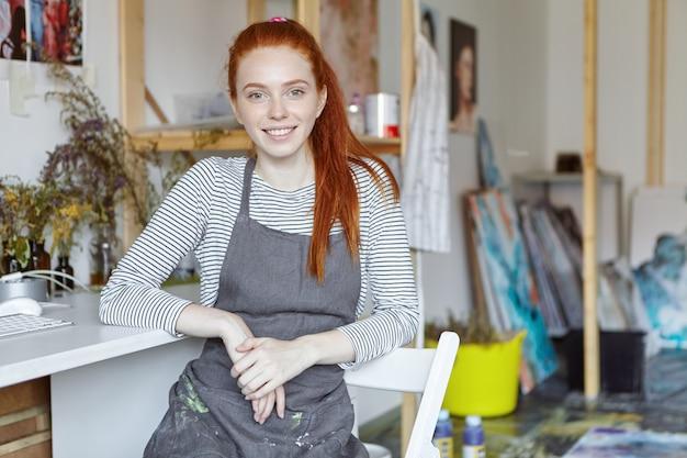 きれいな顔とかわいい笑顔のエプロンを身に着けている才能のある若い工芸品の女性の写真。モダンなクリエイティブなワークショップのインテリアで椅子に座って、仕事を終えた後、絵の具で汚れたエプロンを着て休んでいます。