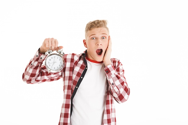 Изображение подростка 16y в случайном холдинг будильника и схватившись за лицо, как опоздание на урок, изолированных на белой стене