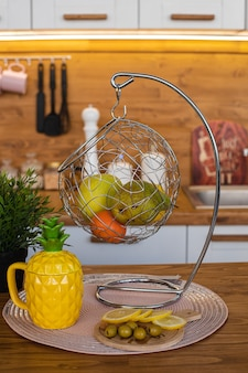 黄色いパイナップルのやかん、白いペッパーミル、果物とぶら下がっている金属を備えた白と茶色の食器棚のある大きな明るいキッチンの写真