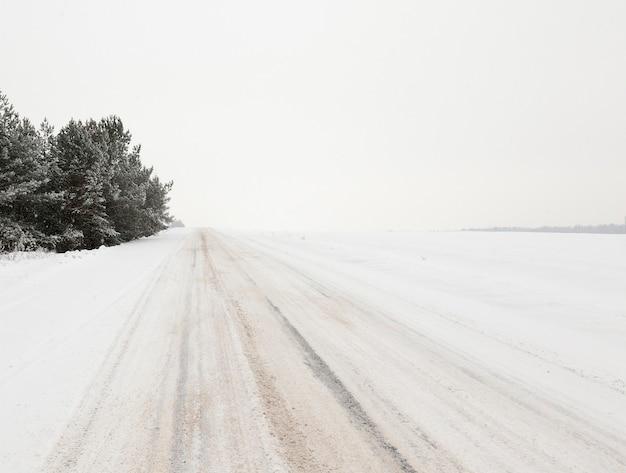 冬の道の写真。車のタイヤから見える雪に覆われたアスファルトの縞模様のクローズアップ