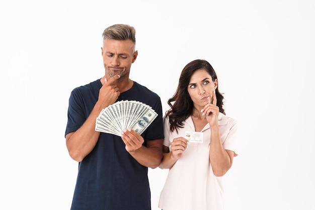 お金とクレジットカードを保持している白い壁に隔離された深刻な大人の愛情のあるカップルを考える写真。