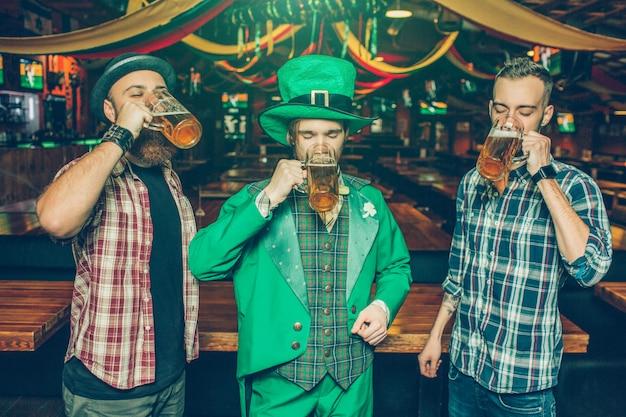 3人の若者の写真がパブで一緒に立って、マグカップからビールを飲みます。彼らは集中した。ミドルの男は聖パトリックのスーツを着ます。