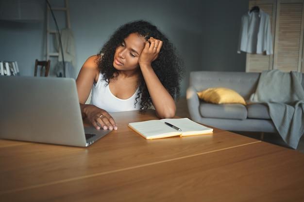 開いた電子機器を持って机に座って、テストの準備をしている間疲れを感じている疲れた美しい若いアフリカの女子学生の写真。人、技術、教育、仕事、職業