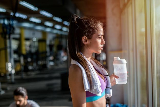 Изображение усталой спортивной женщины, смотрящей через окно в тренажерном зале и отдыхающей после тренировки.