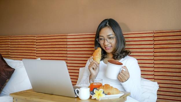 Изображение туристов, завтракающих и использовавших ноутбук на кровати в роскошном гостиничном номере, концепция здорового питания.